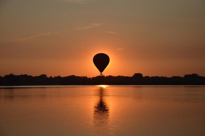 Ballon voor zon - Luchtballon kruist voor de zon langs tijdens de zonsondergang. Haarrijnse plas bij Vleuten.