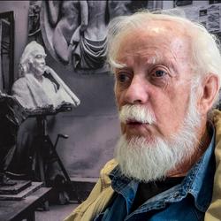 beeldend kunstenaar kijkt naar een expospostie van een vriend in Museum Kranenburgh