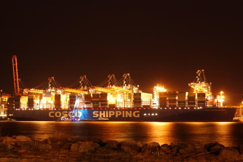 Late dienst op de Maasvlakte - Laden van zware constructiedelen met drijvende bok op giga groot containerschip bij Euromax-terminal op de Maasvlakte.