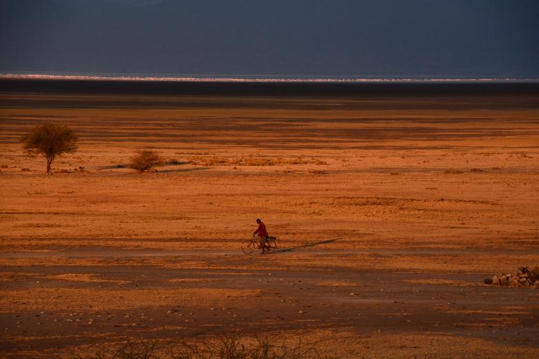 Lake Manyara - En daar zat voor hooguit 30 seconde een gat in de wolk zodat ik deze eenzame wandelende fietser over het droge deel van Lake Manyara me