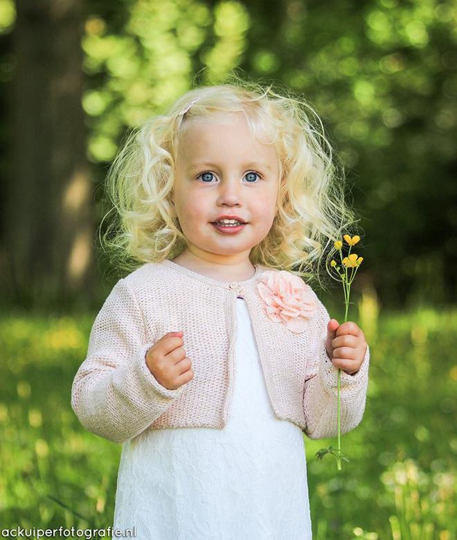 Park - Meisje met een bloempje in haar hand tijdens een wandeling in het park