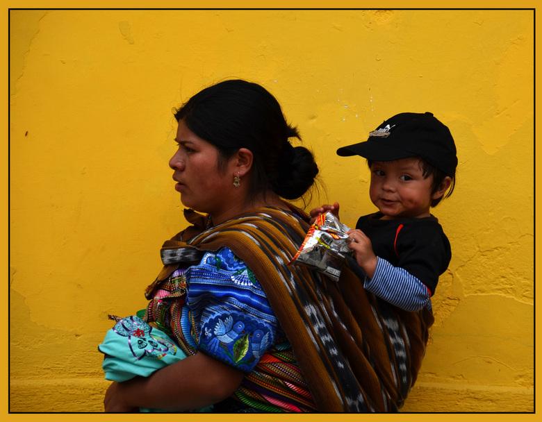 Feest - Deze jongeman, op moeders rug, geniet van een tractatie nl. van een zakje chips. <br /> Deze foto is genomen in Antiqua (Guatemala) op de eer