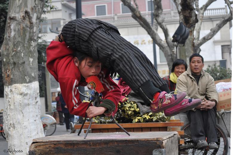 Straatcircus in China 1 - Een jong meisje draait met haar mond-draaimolentje in het rond in de straten van Hangzhou, China.