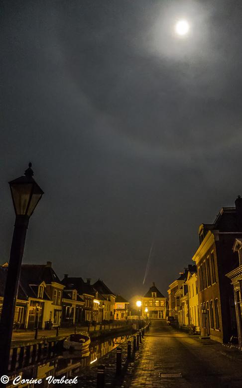 Supermaan - Nacht opname van &#039;de Wallen&#039; in Kollum met een supermaan met krans en een &#039;vallende ster&#039; (schijnsel van de lantaren <
