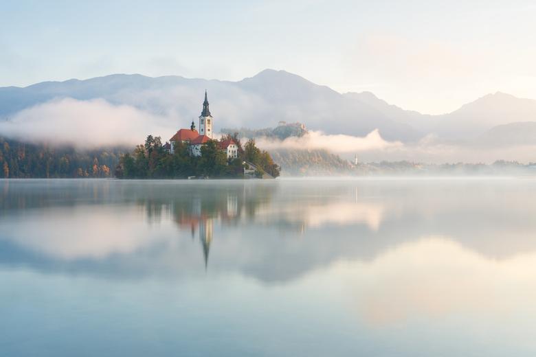 Bled´s sprookjesachtige ochtend  - Gefotografeerd op een kalme morgen bij het meer van Bled. De opkomende zon samen met de laaghangende wolk zorgt erv