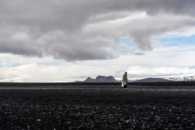 Shopping - Lonely man at the black beach of Vik in Iceland