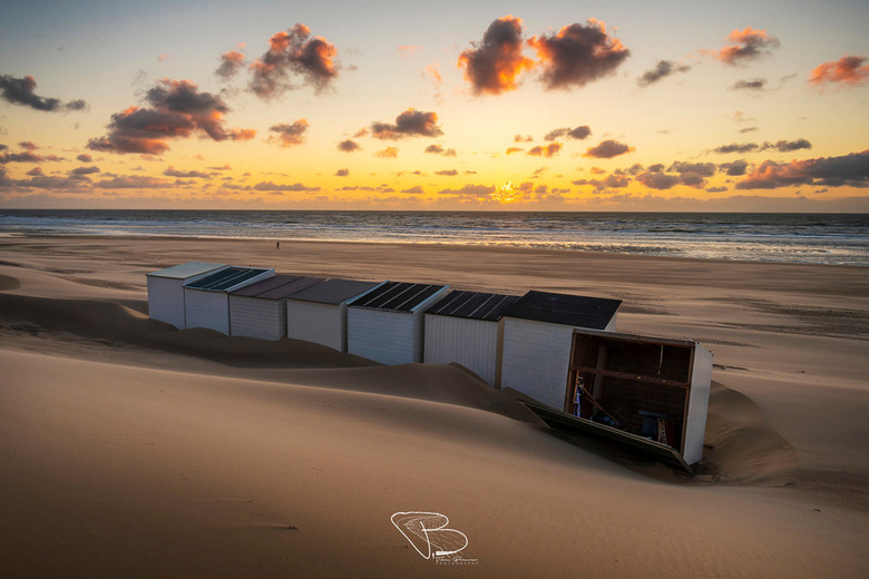Odd One Out - Een kleurrijke zonsondergang, nadat de wind een van de strandhuisjes heeft omgewaaid eerder die dag.