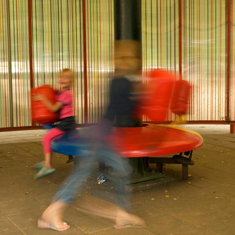 In beweging - Mijn beide kleindochters op de draaimolen.
