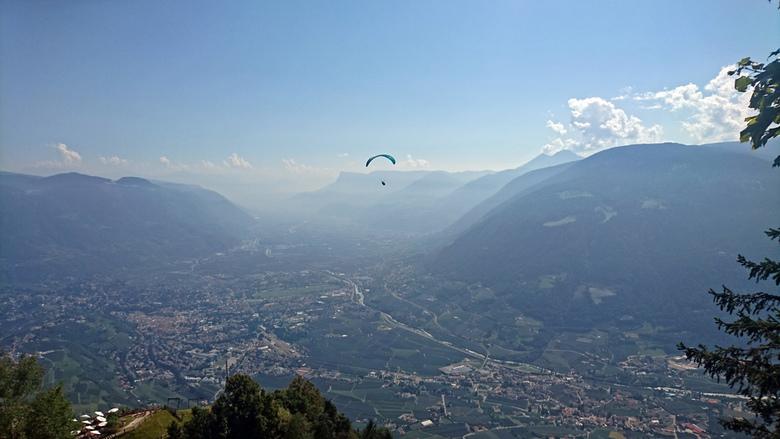 Vrijheid - Parasailen boven Merano in de Italiaanse Alpen. Foto is genomen langs de route van de Meraner Hohenweg