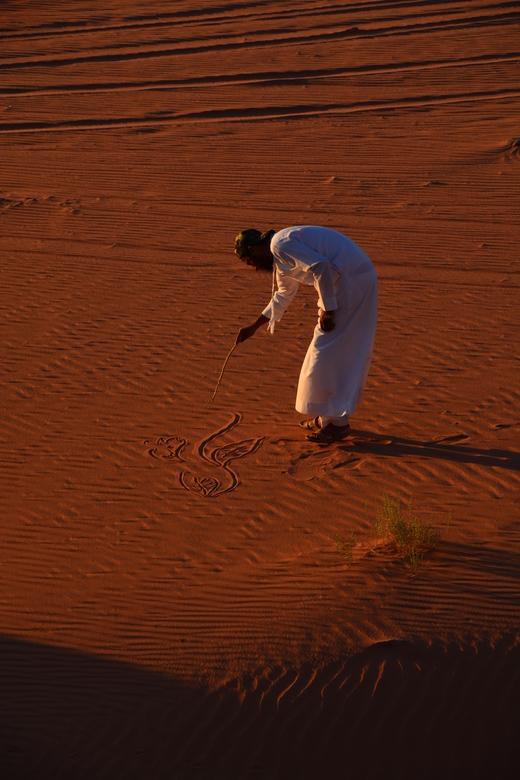 WadiRum kunstenaar - Tijdens het wachten op de zonsondergang zag ik onze gids ineens met een stok in de hand bloemen aan het tekenen in het zand. Een