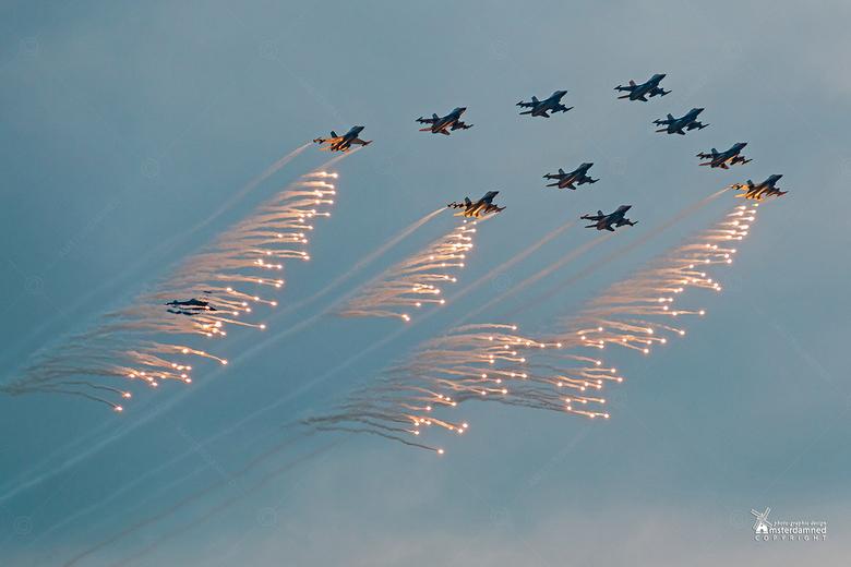 Luchtmachtdagen Volkel 2019 - Een formatie F16's schiet flares af tijdens de Luchtmachtdagen 2019 in Volkel. In laatste positie, half verschollen