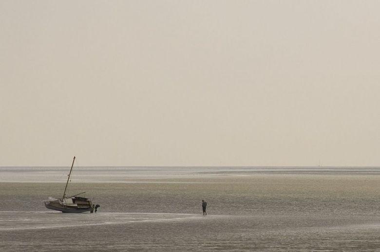 Man op het water - De eenzame man loopt rustig over het water, wachtend op de vloed. Geen stress, even een moment voor jezelf.