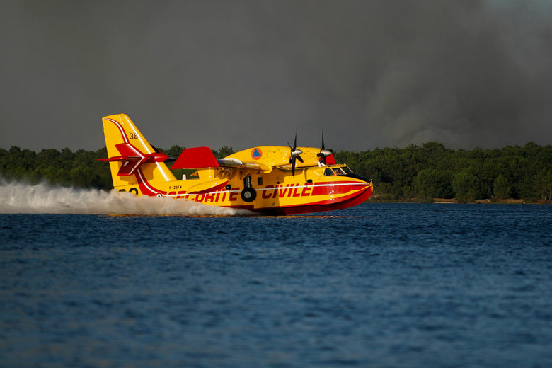 Blusvliegtuig 2 - Blusvliegtuig op het Etang de Lacanau met een avondzon en de dreigende rookwolken vanuit het achterliggende bos.