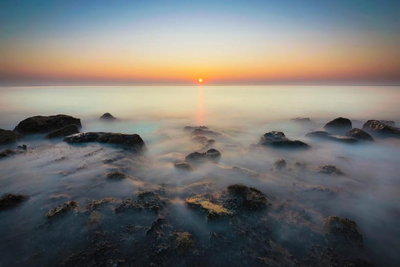 Nebula - Een heldere zonsondergang aan de kust bij Westkapelle. Door de lange sluitertijd vormen de golven zich als een mist om de rotsen van de dijk.