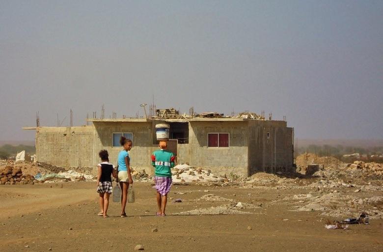Naar huis - Een deel van een Kaapverdische gezin stapt naar hun woning. Het meisje in het midden kijkt toch even achterom. Een schreeuw om aandacht vo