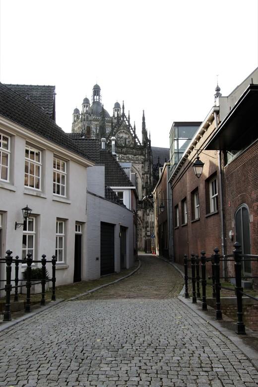 zicht op de st jan  - zicht op de st jans kerk in s-hertogenbosch van uit een smal straatje met oude huisjes en een bruggetje over de dieze<br /> 14-