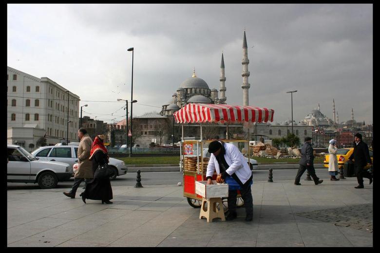 Kraampje met moskeeën op de achtergrond - Een leuk straatbeeld van Istanbul. Een kraampje waar een man eten verkoopt en twee grote moskeeën op de acht