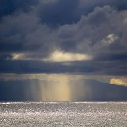 Regen boven zee