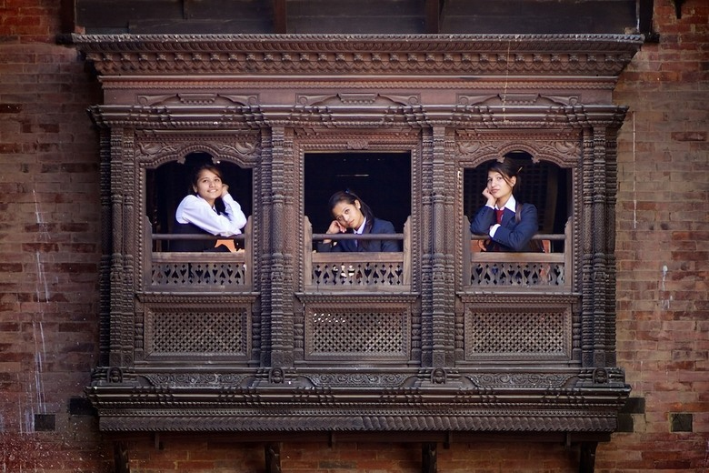 In contrast - Girls in contrast with this old wooden house. In Kathmandu, Nepal.