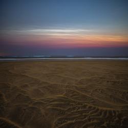 Lichtende Nachtwolken met zeevonk en mooie zandstructuur.
