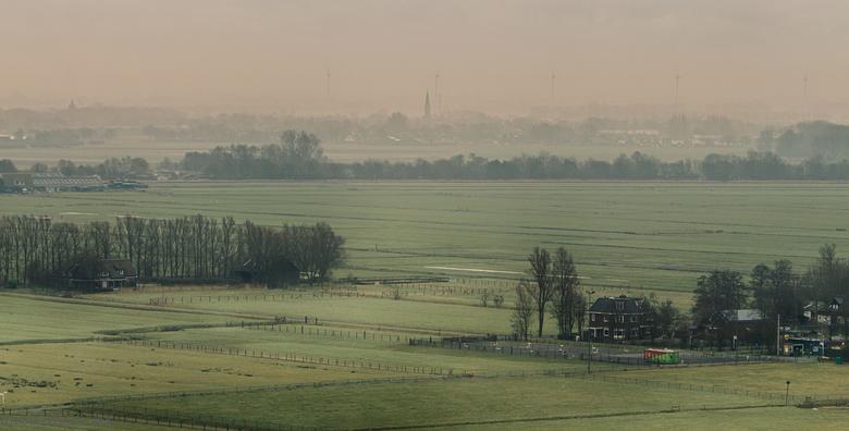 langzaam de mist zien vertrekken over het landschap - Schoorl wordt langzaam wakker, kijkend naar de kerk van wamenhuizen