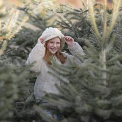 Lachend meisje tussen winterse kerstbomen