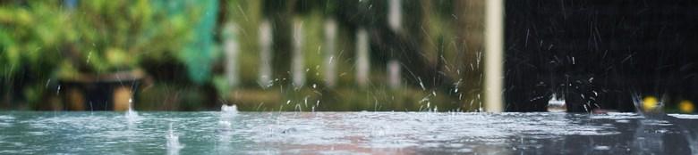 Regen - De druppels kletteren op de tuintafel.