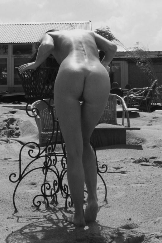 For real - Zwart wit foto van een vrouwelijk model voorovergebogen. Buitenopname
