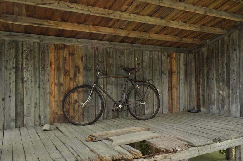 Fiets in een schuur langs de weg waar melk werd opgehaald - Oude fiets in een melkschuur langs de weg waar vroeger de melk werd opgehaald in Noorwegen
