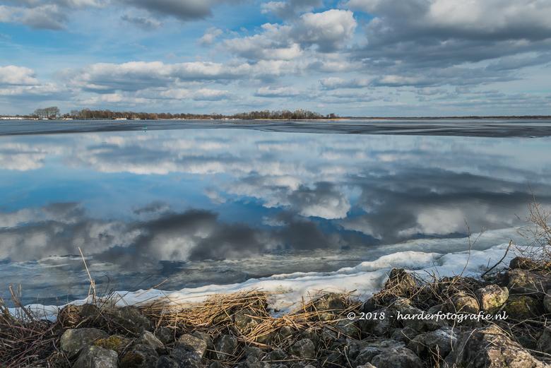 Fraaie wolkenpartijen spiegelend in het water