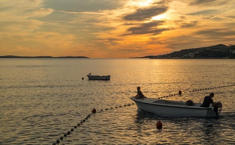 Vader en zoon - Vader en zoon gingen uit varen tijdens de zonsondergang, terwijl wij met nog wat andere Hollanders toekeken vanaf het terras..