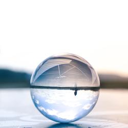 Fietser in spiegelbeeld in glazenbol.