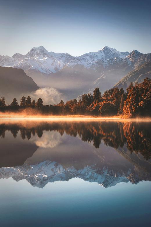 Floating World - Tijdens een heldere zonsopkomst weerspiegelt Mount Cook prachtig in het water van Lake Matheson, Nieuw-Zeeland. Het goudgele ochtendg