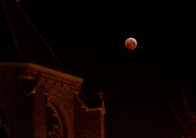 Bloedmaan_grote_kerk_Venray - Met een klein stukje van de grote kerk in de voorgrond is de bloedmaan mooi te zien aan de hemel.
