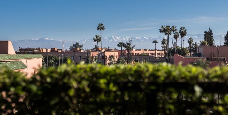 Marrakesh Atlas 2 - Een paar gebouwen van Marrakesh, Marokko. Op de achtergrond is het Atlasgebergte duidelijk te zien en zorgt voor een plaatje dat e