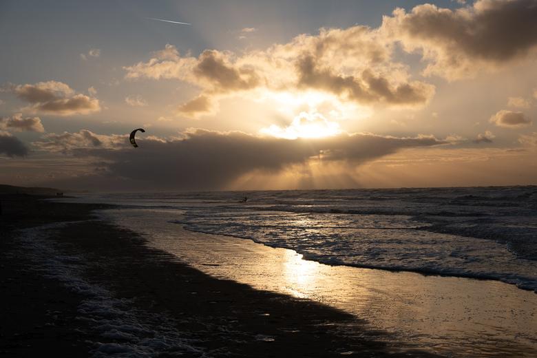 Kite surfen bij zonsondergang - Harde wind en een rustige zonsondergang