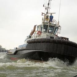sleepboot die de Ovation of the seas verwelkomt