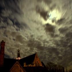 Maan beschijnt kerk door wolkendek