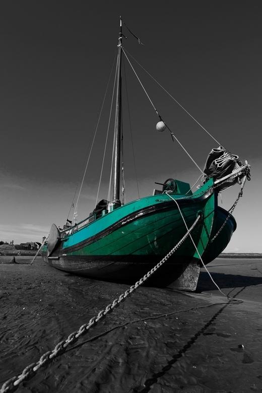 Groen - groene boot op het groene strand