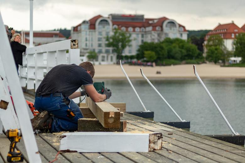 Het werk gaat altijd door - Het werk gaat altijd door, ook al zijn er veel toeristen. Dit is op de pier in Sopot in Polen.