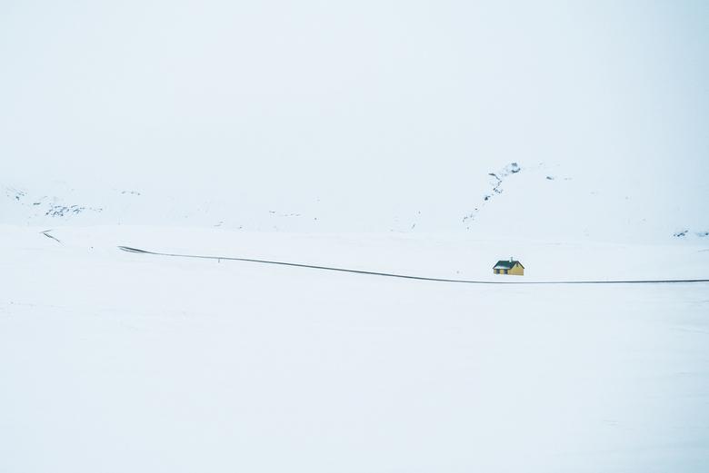 Het is eenzaam aan de drukke weg - Een klein huisje staat alleen op het, met sneeuw bedekte landschap.