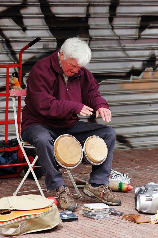 Trommelaar - Uitstapje naar straat fotografie. Deze trommelaar was zo opgegaan in zijn trommellen tijdens Koningendag. Ik vond het wel een leuk totaal