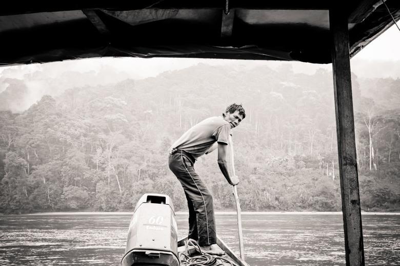 Amazone avontuur - Tijdens een 5-daagse tour door Manu National Park in Peru loodste deze man onze boot door het ondiepe water.