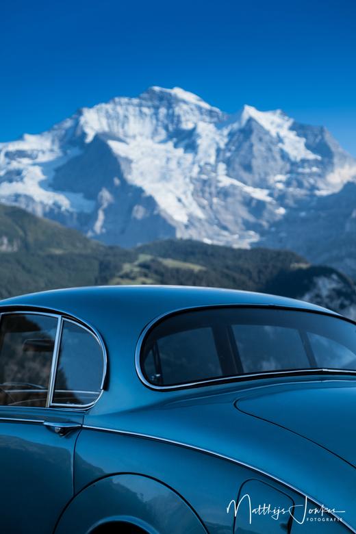 Een oude Jag in de Swiss Alps - Een oldtimer met op de achtergrond een nog oudere oldtimer, ironisch genoeg genaamd Jungfrauhöhe.