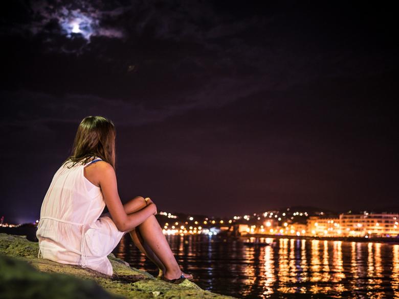 Kijkend in de nacht - Uitkijkend over het water op de nachtelijke kustlijn, <br /> met de maan boven zich die door de wolken schijnt, <br /> zit op
