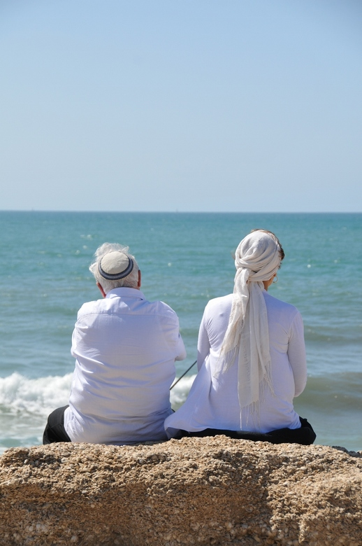 wegdromen - Joods echtpaar kijkt uit over de zee aan de kust bij Tel Aviv