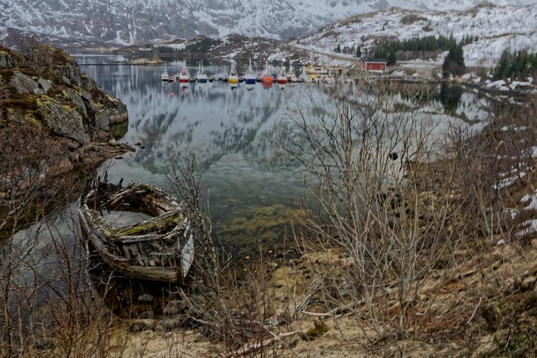 Gestrand - Karkas van een vissersboot, die is gestrand op de Lofoten. In de verte ligt een haventje waar nieuwe boten aangemeerd liggen. Mooi landscha