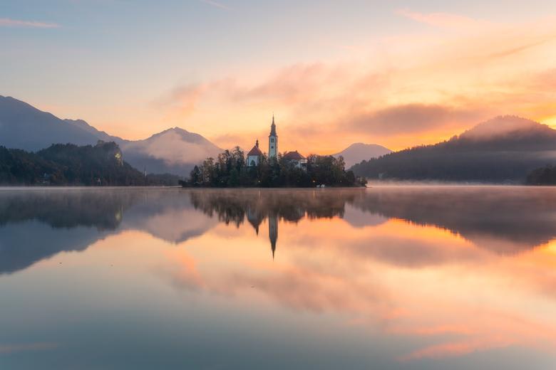 Bled´s magische morgen - Een prachtige zonsopgang weerspiegelt in het meer van Bled, Slovenië.
