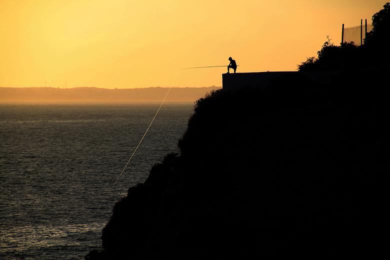 Visser bij zonsondergang - Een visser aan de zuidkust van Portugal.