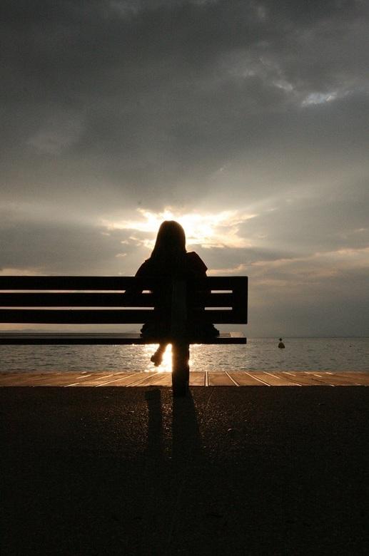 Silhouette van een meisje aan het water. - Foto genomen in Bardolino bij zonsondergang, mijn zusje zat op het bankje en met de zon erachter kreeg ik d